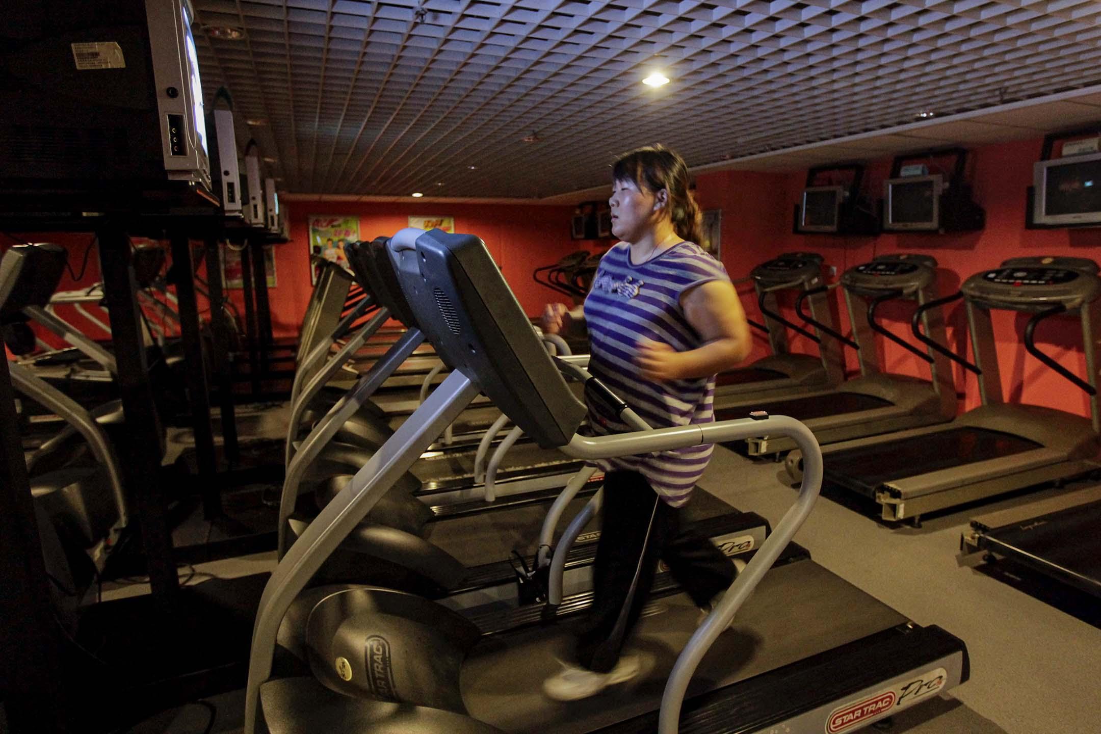 2011年8月26日,一名婦女在健身室的跑步機上跑步減肥。