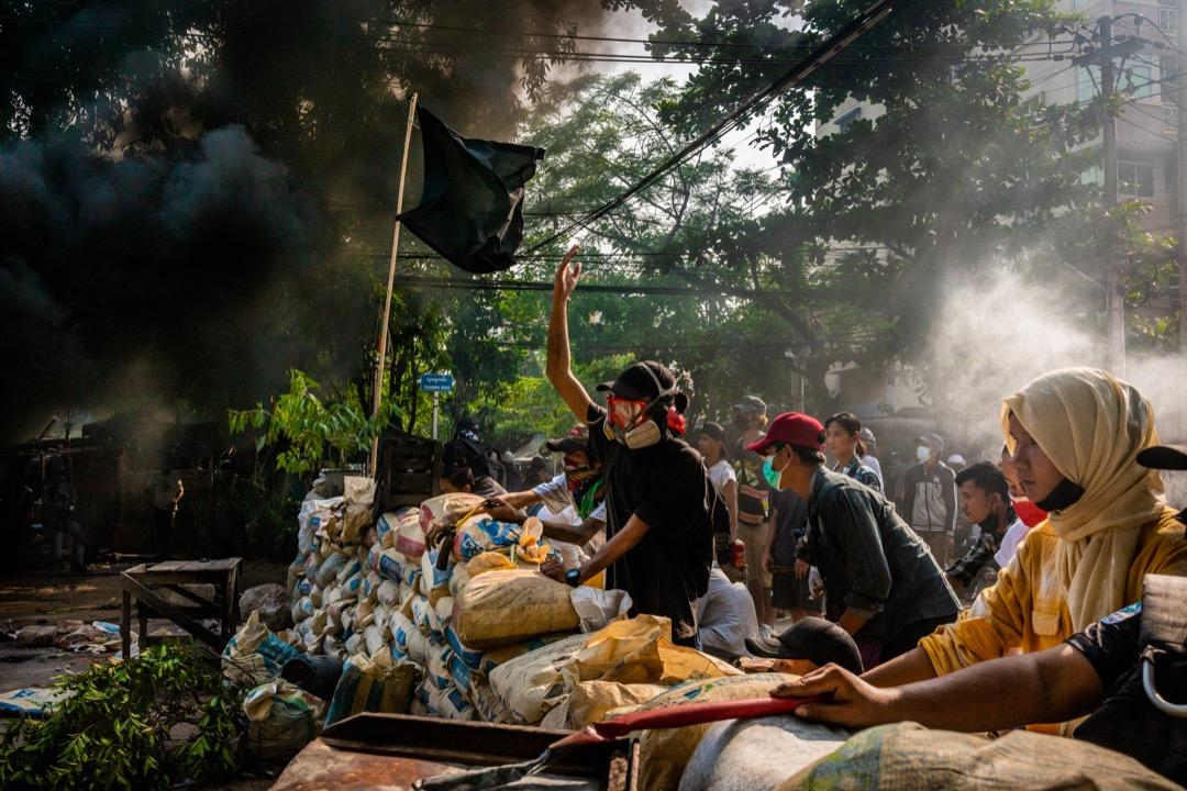 2021年3月28日,緬甸仰光,反軍政府示威者在路上築起障礙物、焚燒車胎堵路,並向迎面而來的安全部隊大喊口號。