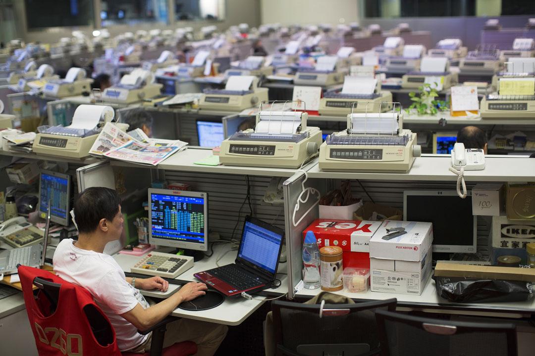 2013年8月13日,一名股票交易員在港交所交易大堂的桌上看着手提電腦。