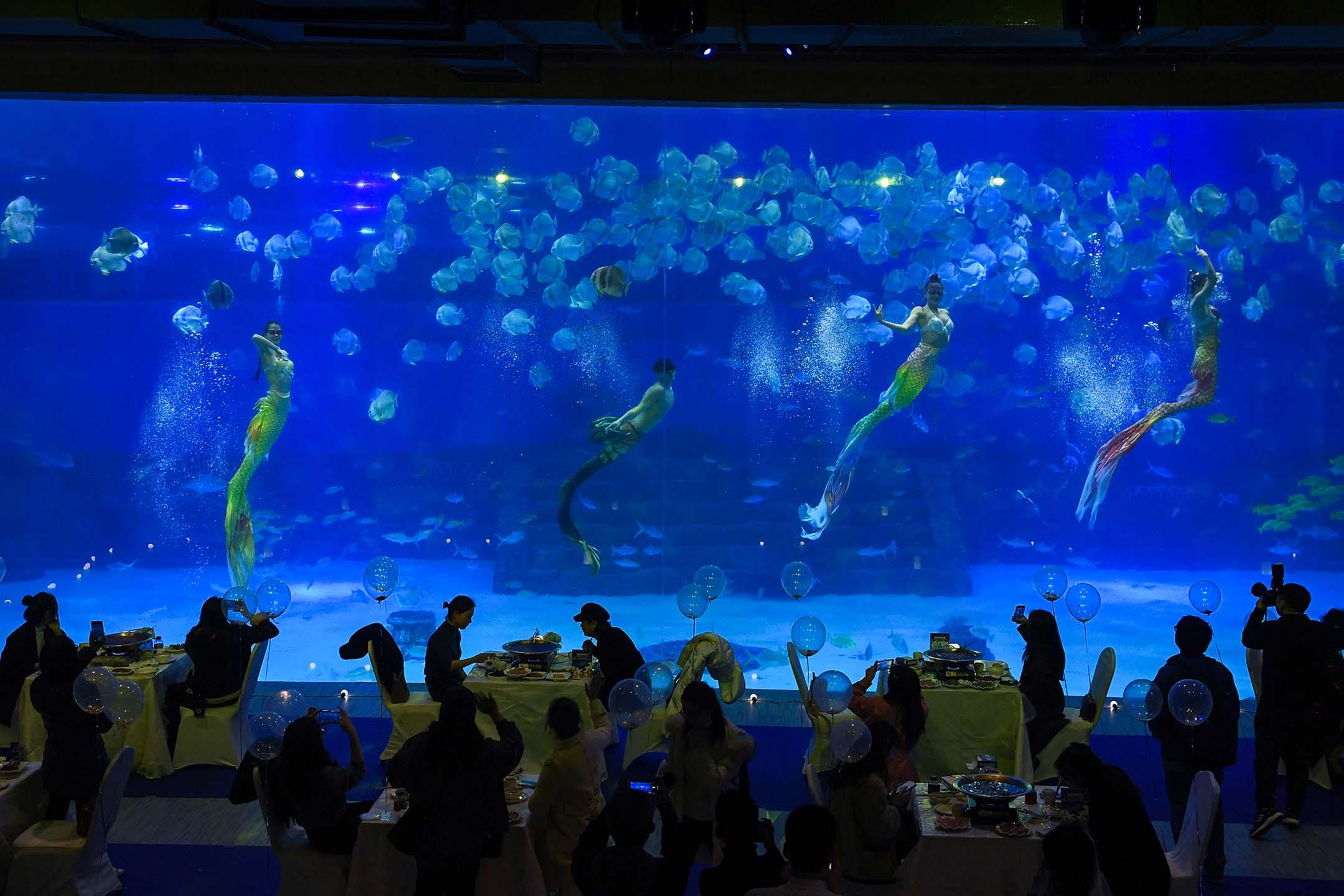 2021年3月8日重慶,國際婦女節,婦女在觀看美人魚表演。