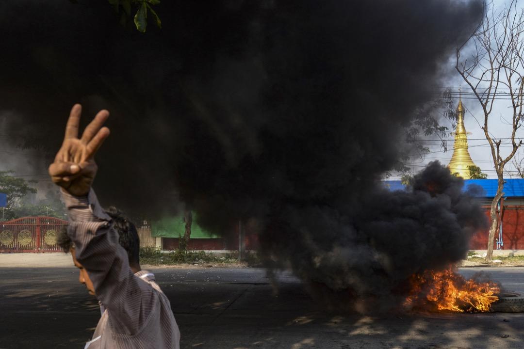 2021年3月24日,緬甸仰光,反軍政府示威者焚燒雜物堵路,一名路人舉起三指手勢表示支持。