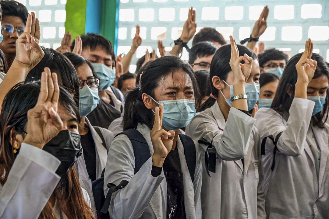 2021年3月16日,緬甸仰光舉行的示威者葬禮上,醫學院學生舉起三指敬禮。