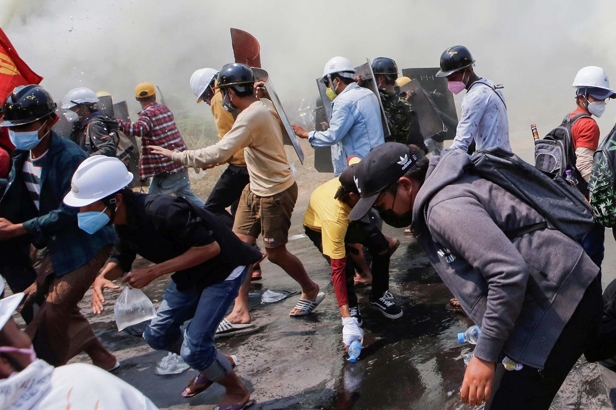 2021年3月8日緬甸奈比多,一場軍事政變示威活動中,示威者在催淚彈和滅火劑氣體中逃跑。