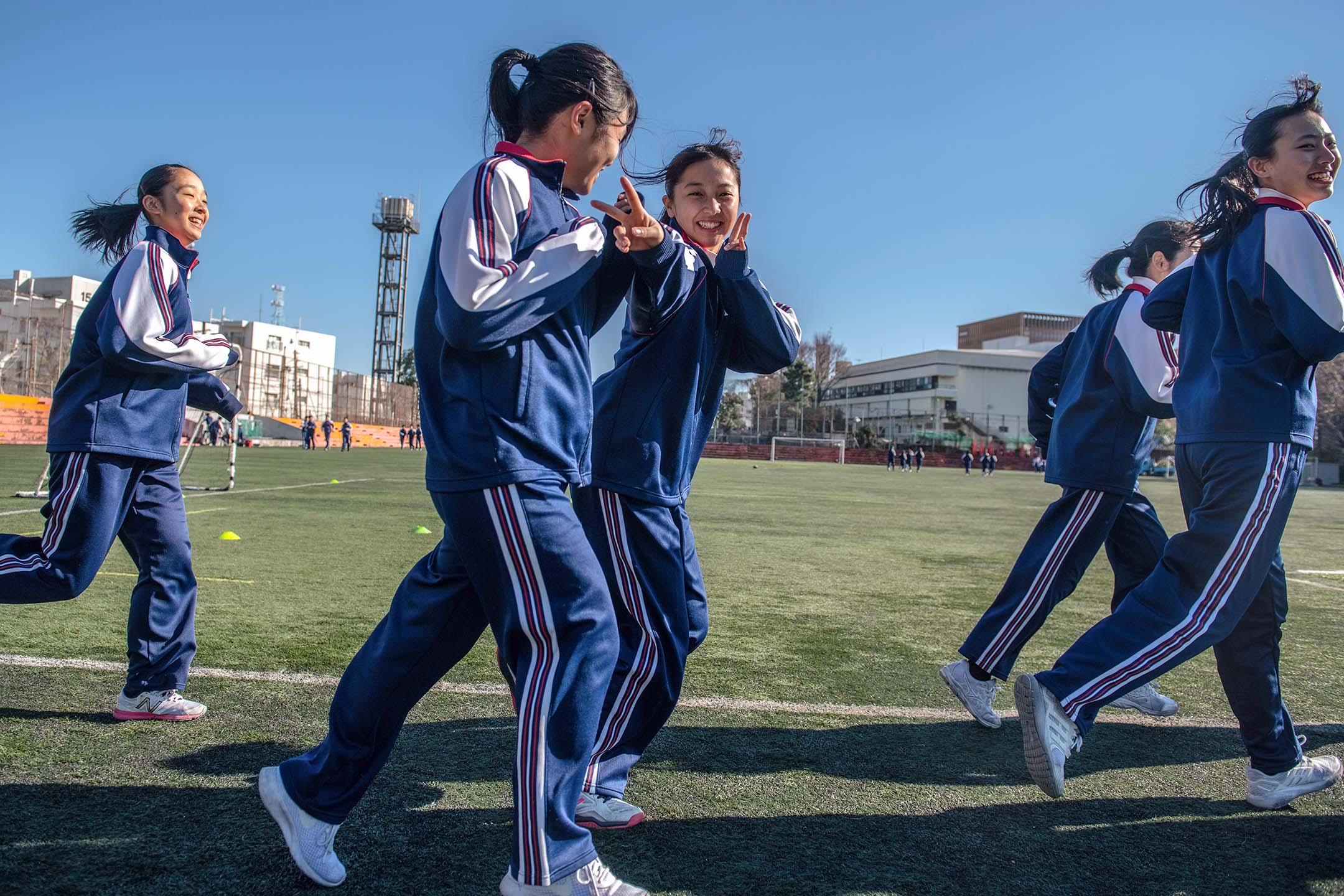 2019年1月22日東京,一群女學生在體育課於學校運動場慢跑。 攝:Carl Court/Getty Images