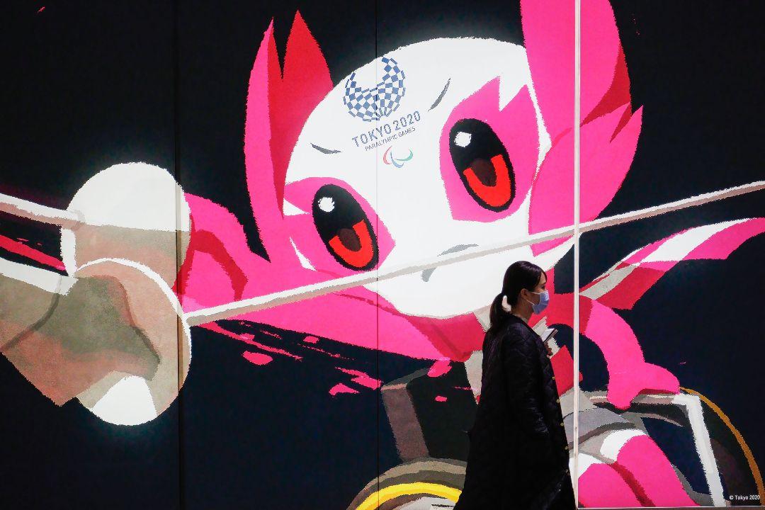 2021年3月4日,日本新宿站,一名女性走過「2020東京奧運會」海報。 攝:James Matsumoto/Getty Images