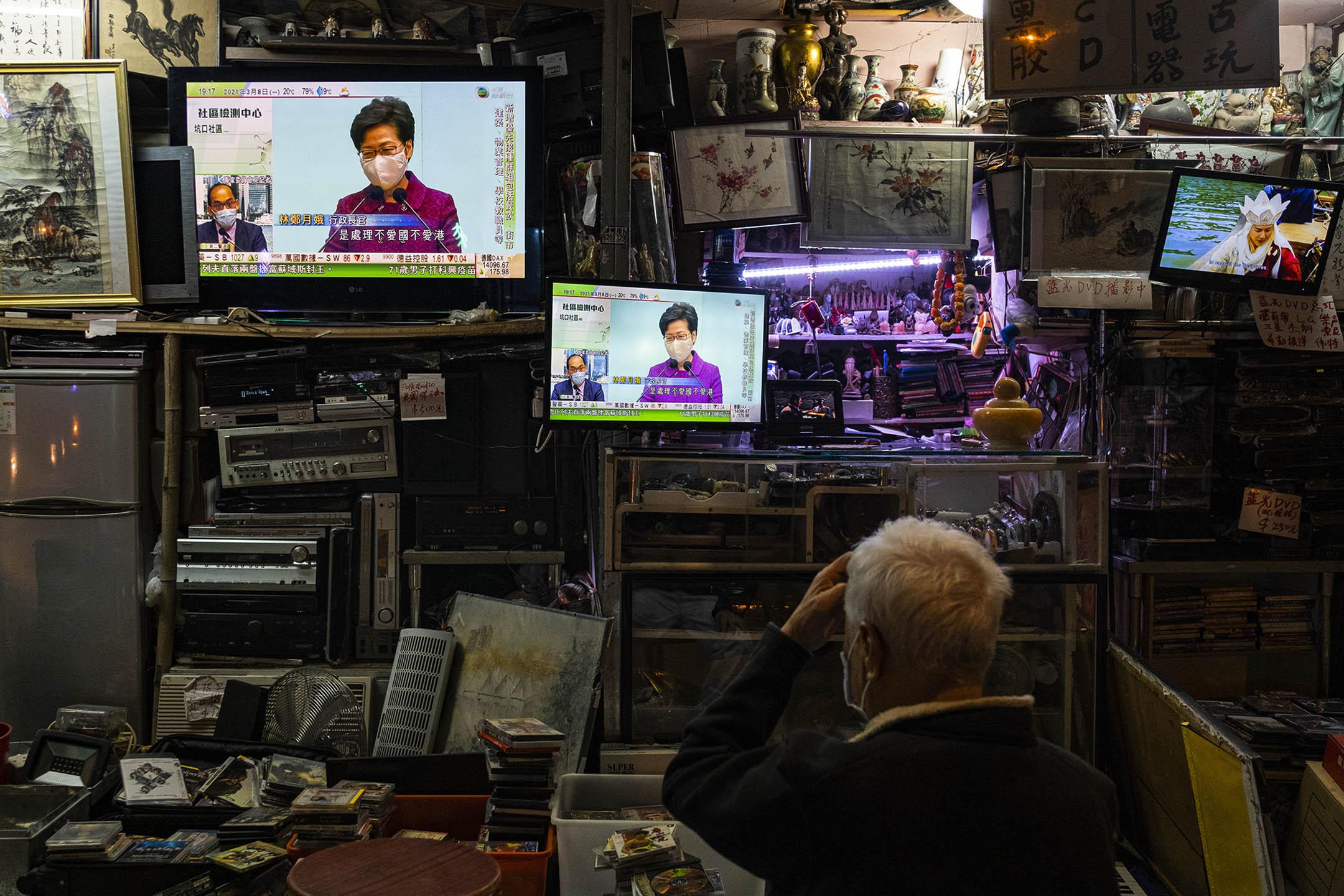 2021年3月8日深水埗,市民在觀看電視新聞報告,特首林鄭月娥於政府總部會見傳媒,就香港選舉制度改革講話。