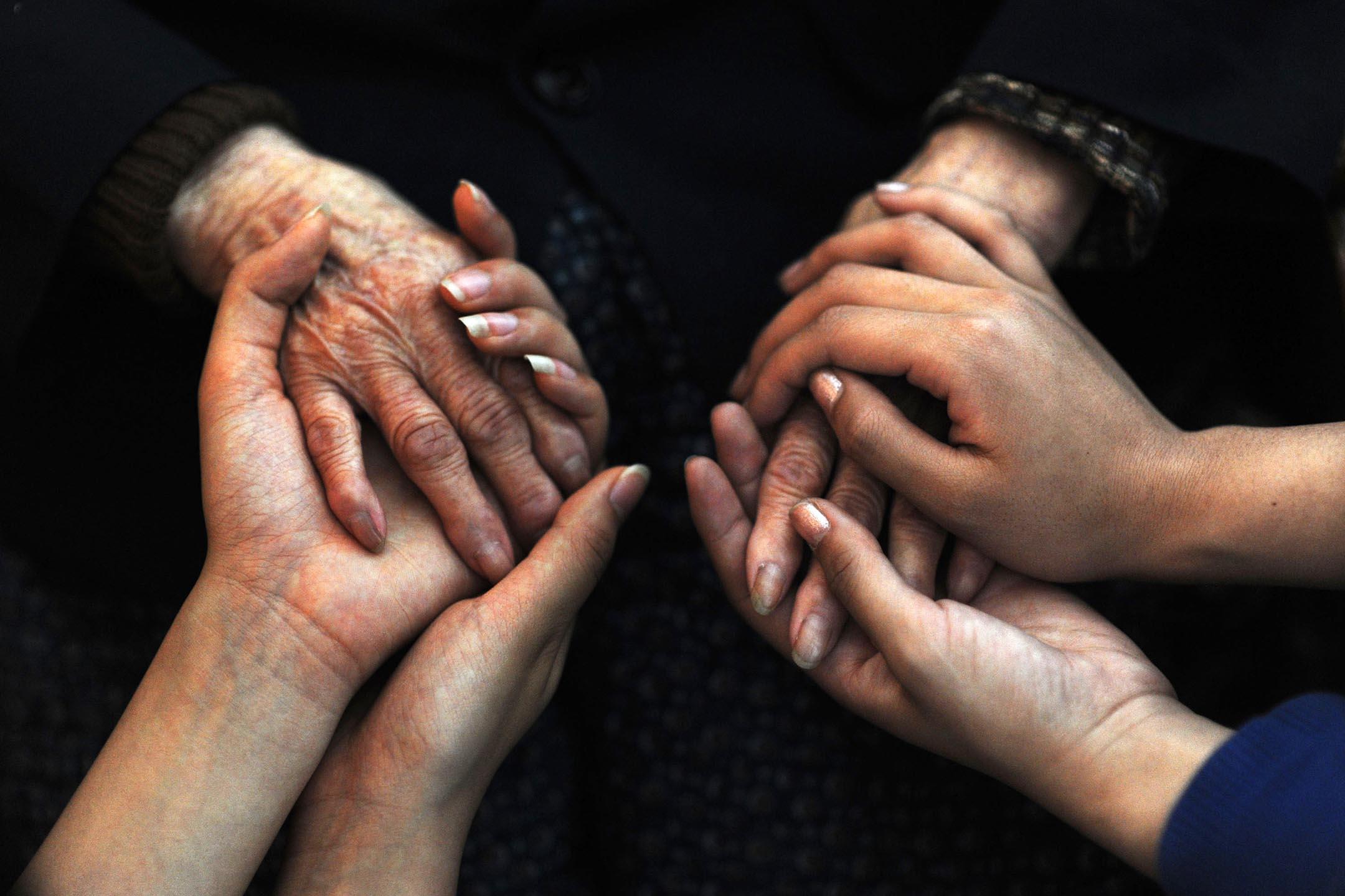 2009年4月18日武漢,志願者在武漢市的福利中心握著老年人的手。