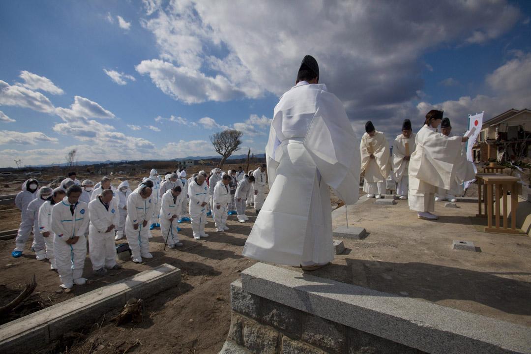 2012年,神道教神父在日本福島海嘯中被摧毀的古草野神社遺址主持悼念儀式,一群來自日本的撤離者到場鞠躬致敬。