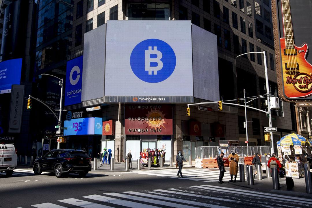 2021年4月14日,美國最大的加密貨幣交易所 Coinbase Global Inc.首日上市,比特幣標牌顯示在一個戶外屏幕上。 攝:Michael Nagle/Bloomberg via Getty Images