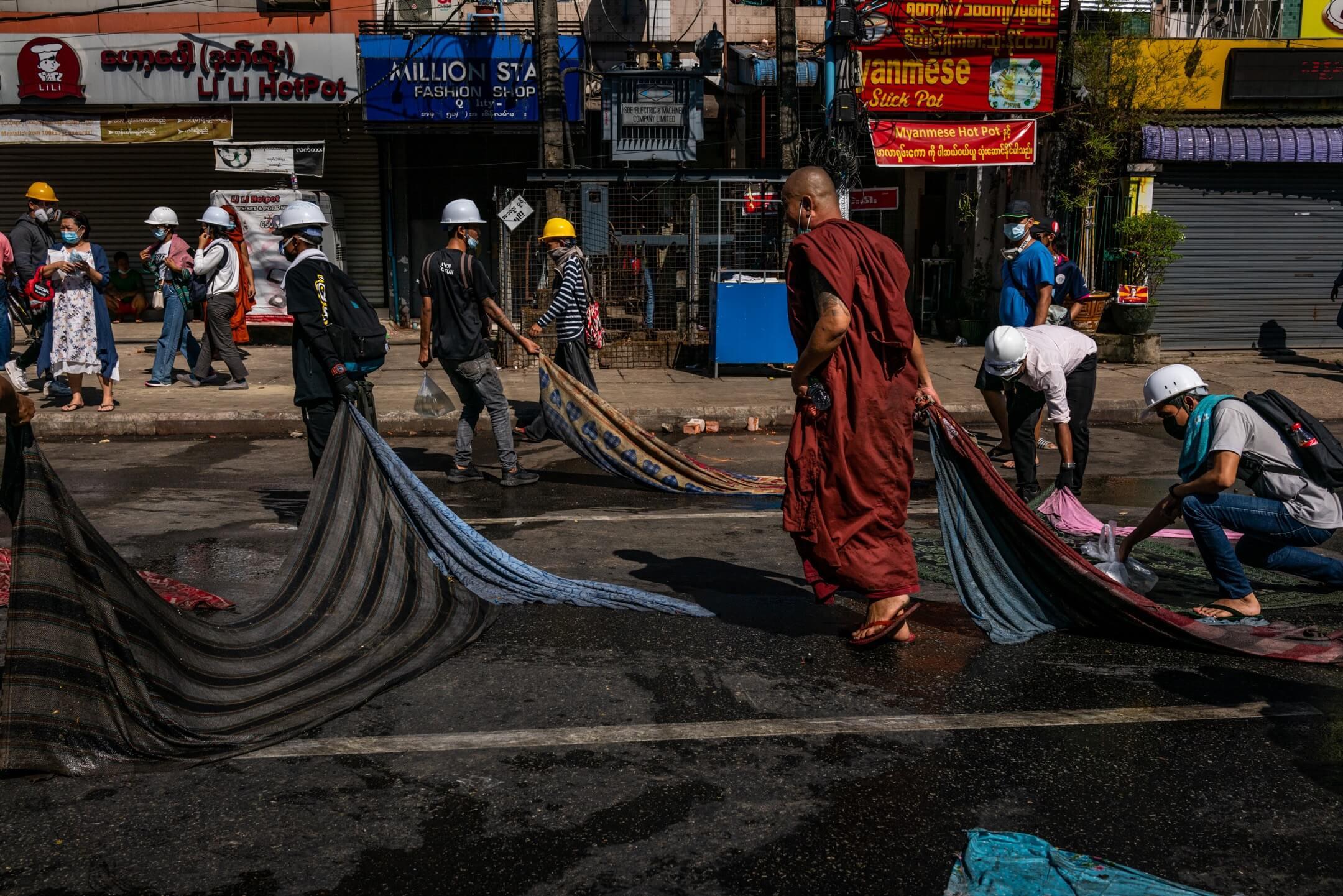 2021年3月1日,緬甸城市仰光,反對軍政府奪權的示威持續,防暴警察驅散示威者後,有市民清理街道上遺下的雜物。 攝:Hkun Lat/Getty Images