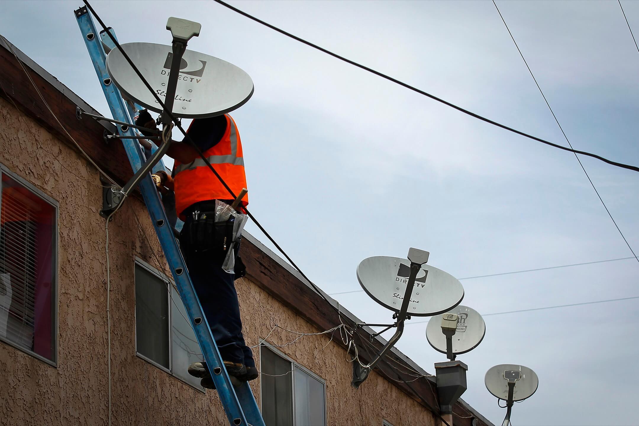 美國加州,一位網絡供應商工人為住戶安裝衛星天線。 攝:Patrick T. Fallon/Bloomberg via Getty Images