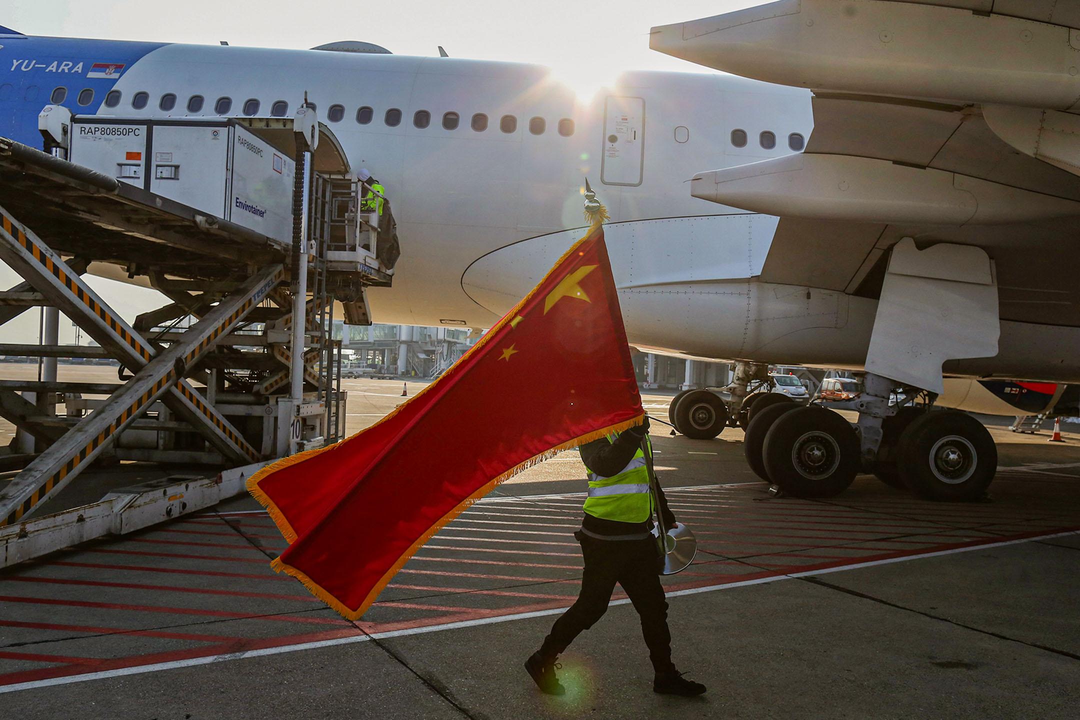 2021年1月16日塞爾維亞貝爾格勒尼古拉·特斯拉機場,100萬劑國藥疫苗到達機場後,一名工人揮舞中國國旗。