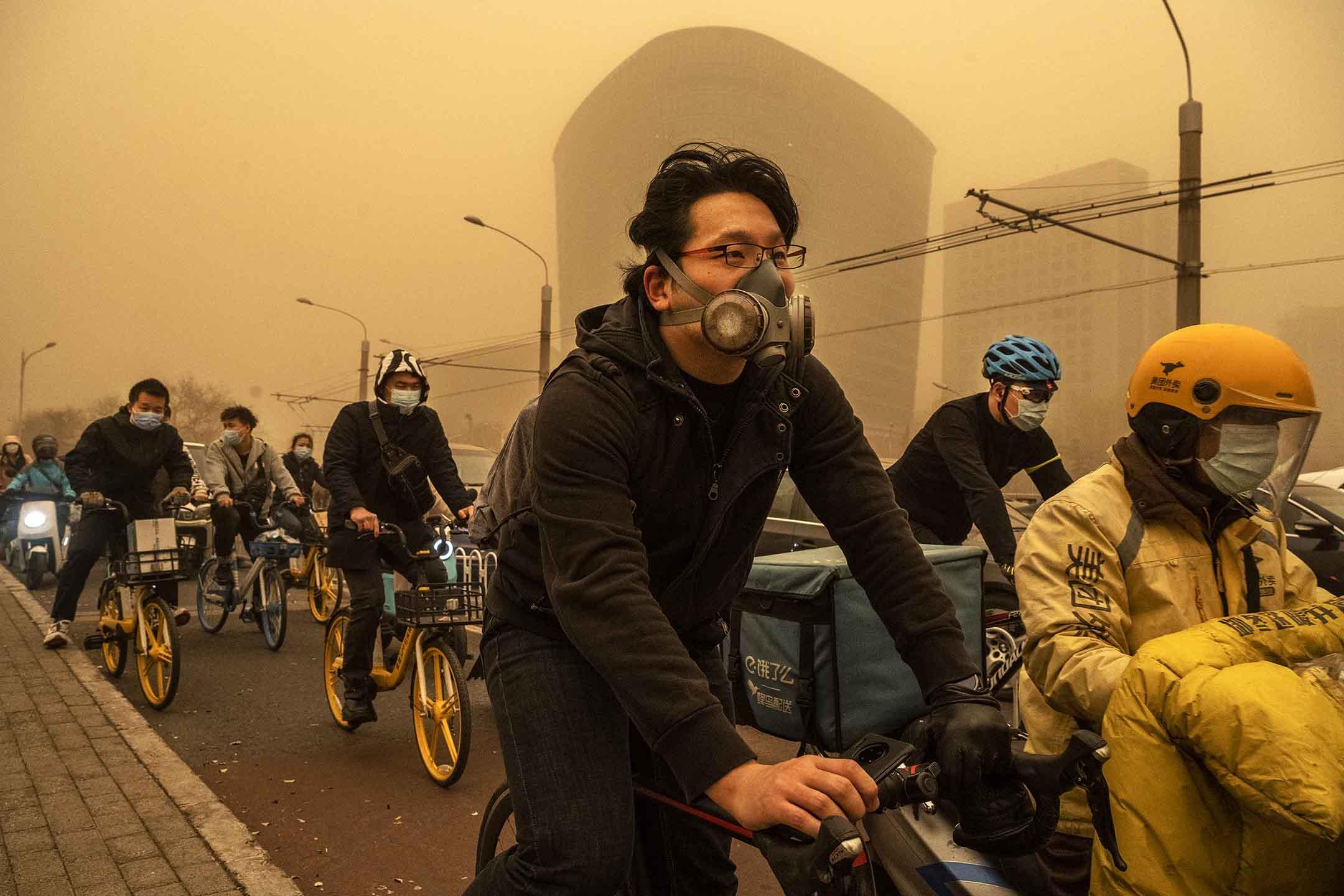 2021年3月15日,北京,人們戴著口罩在沙塵暴期間上班。