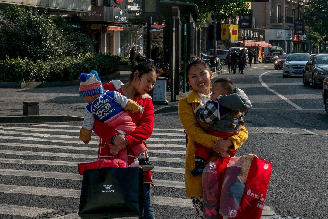 2015年11月17日,中國雲南麗江,兩個年輕媽媽抱着孩子。 攝:Zhang Peng/Getty Images