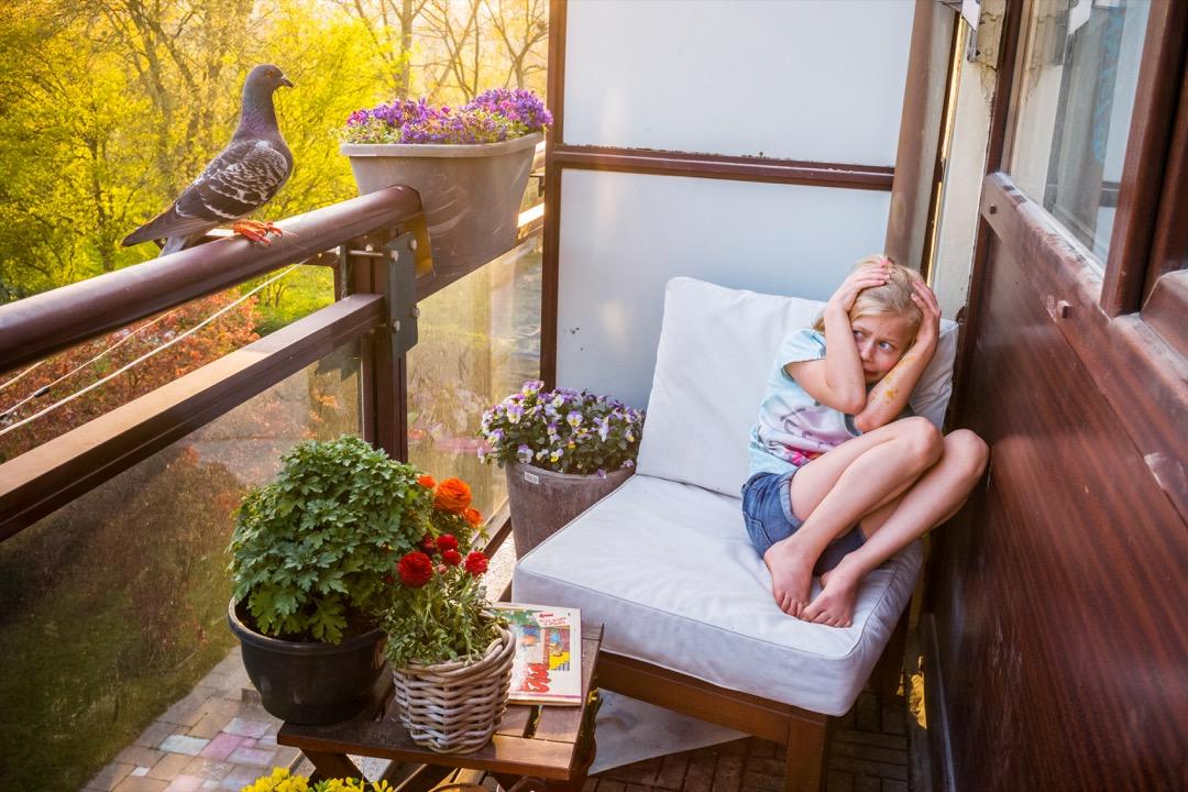 2020年4月6日,荷蘭城市弗拉爾丁恩(Vlaardingen),攝影師的女兒Merel在躲避一隻飛到露台上的野白鴿。