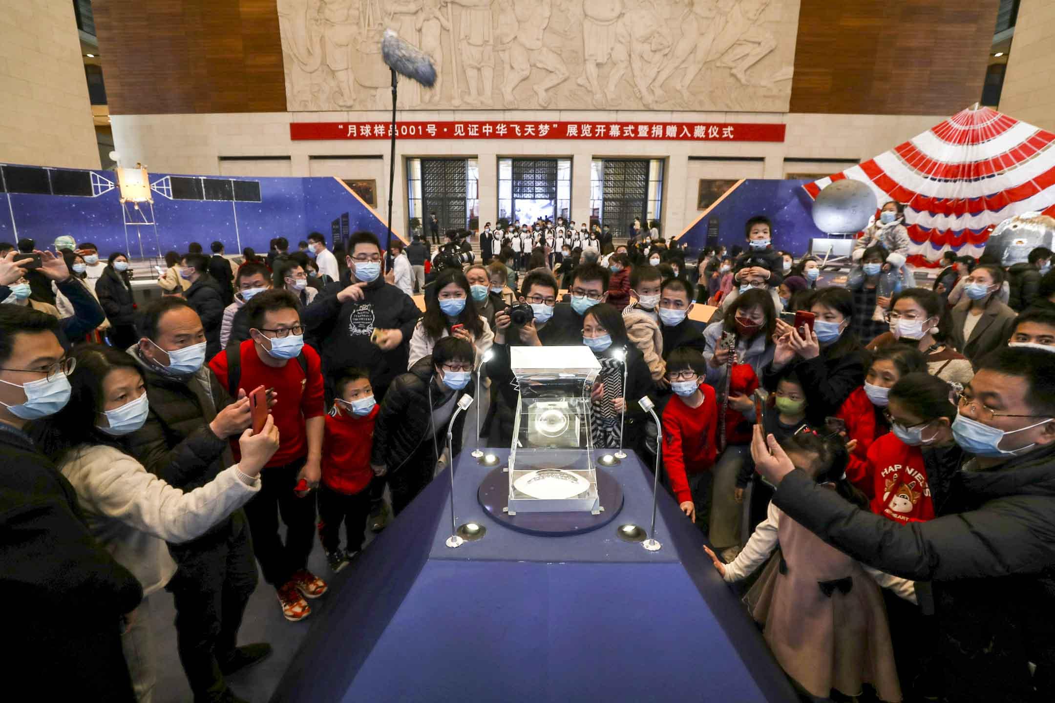 2021年2月27日,北京,人們在中國國家博物館觀看一塊由嫦娥五號探測器從月球表面採集的樣本。 攝:VCG via Getty Images