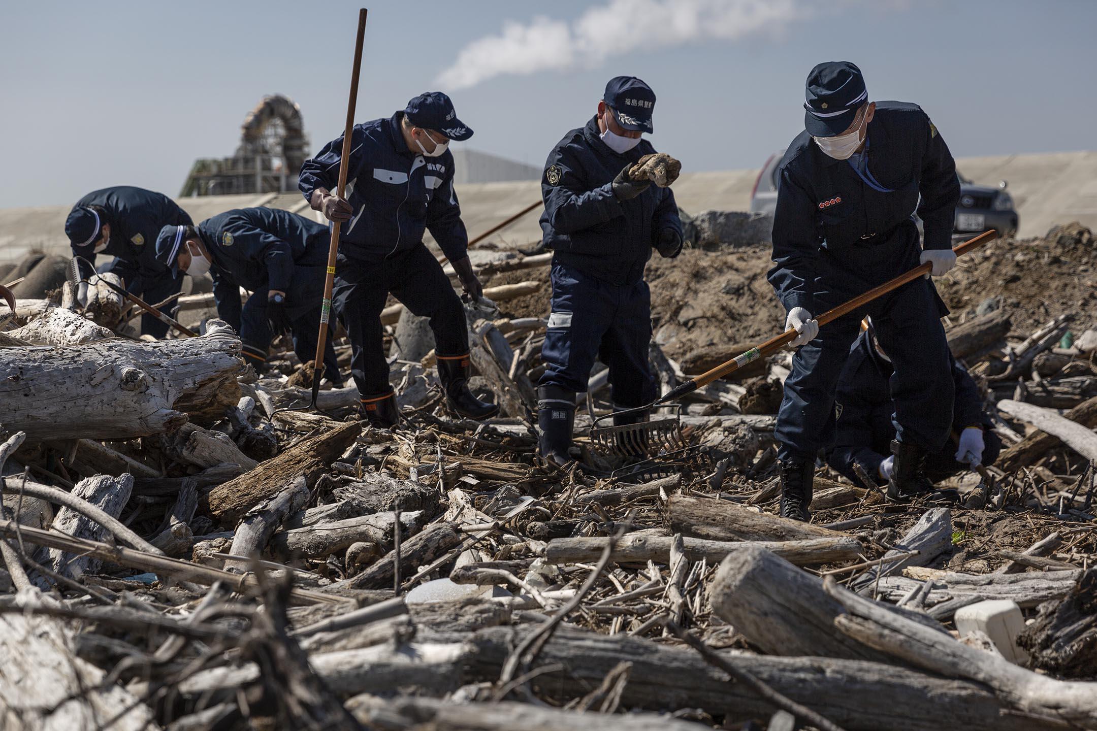 2021年3月11日,日本福島縣浪江町,警員在海邊搜索十年前福島核電廠爆炸事故中失蹤者的遺體。