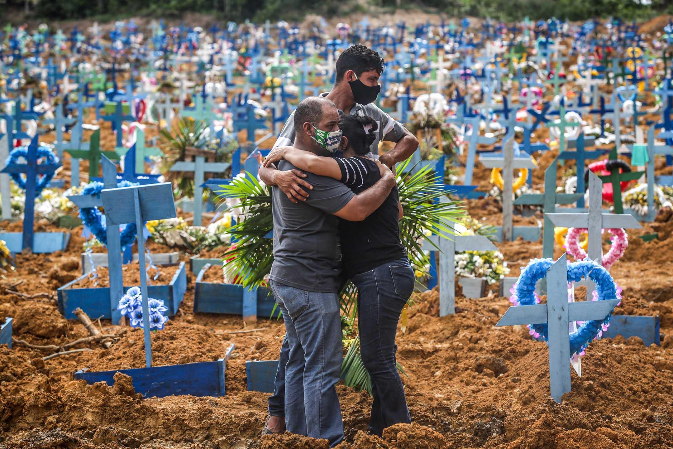 2020年5月19日巴西馬納烏斯的公墓,戴著口罩死者的親屬在哀悼。