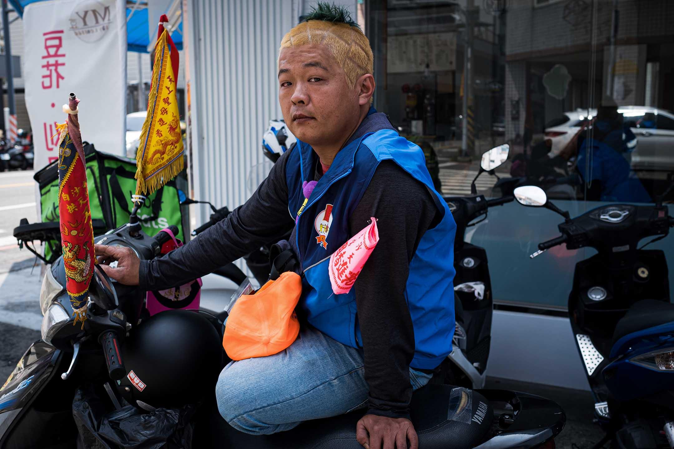 一名信眾在自己的機車上掛了進香旗,參與媽祖進香。
