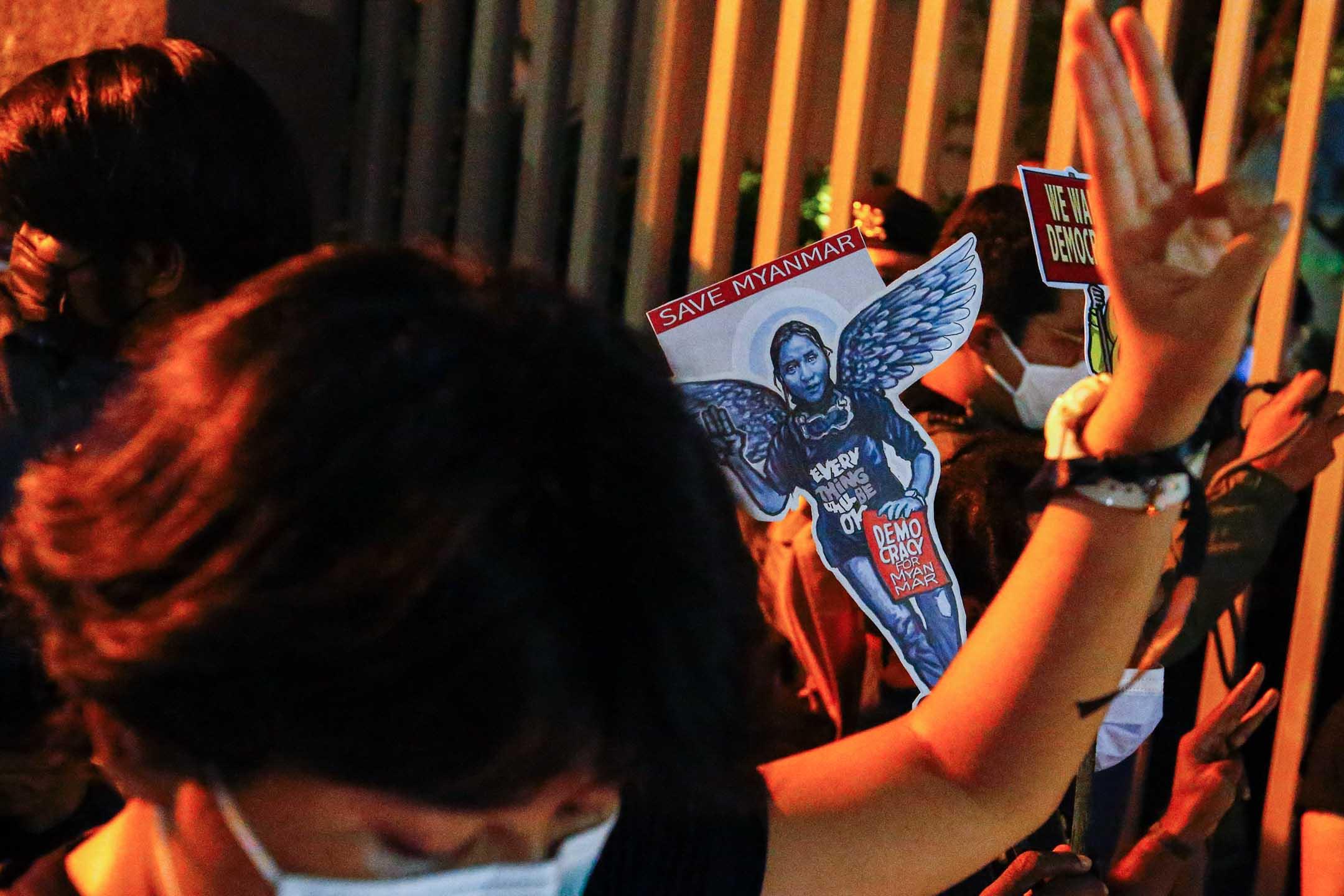 2021年3月12日印度尼西亞雅加達,一名婦女在標語牌旁舉起三指致敬,上面畫著一個抗議者Kyal Sin,她在抗議緬甸軍事政變的示威活動中被槍殺。