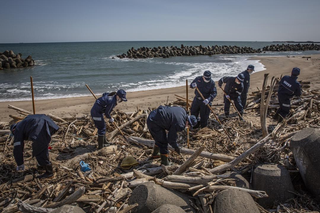 2021年3月11日,日本福島縣浪江町,警員在海邊搜索十年前福島核電廠爆炸事故中失蹤者的遺體。 攝:Yuichi Yamazaki/Getty Images