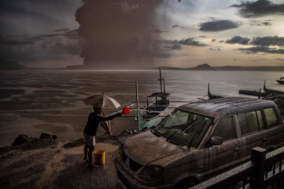 2020年1月12日,菲律賓塔里薩伊市,一名居民向一輛滿佈火山灰的車輛潑水。