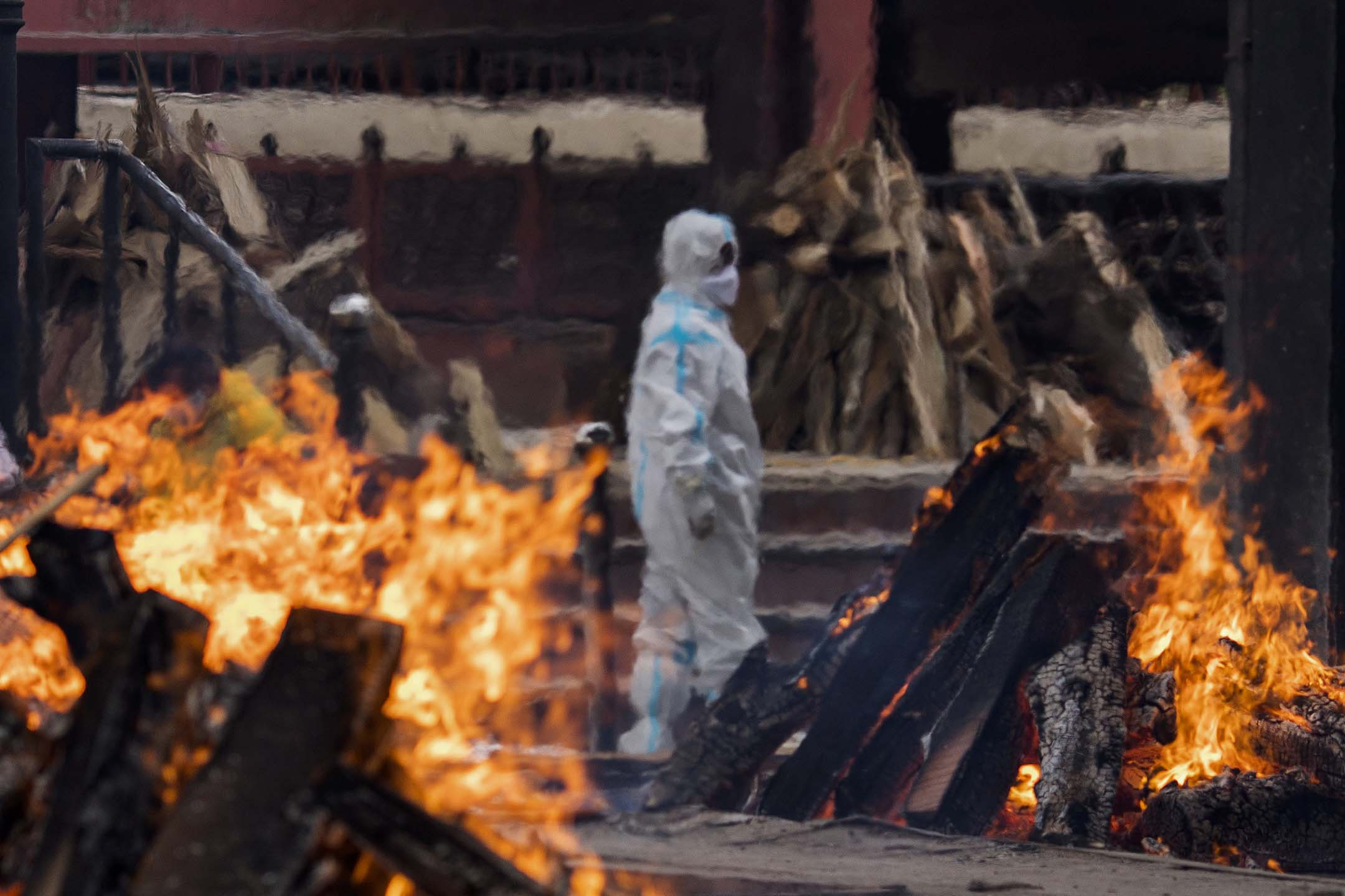 2021年4月20日,印度新德里火葬場内一名穿著防護衣的男子。 攝:Anindito Mukherjee/Getty Images