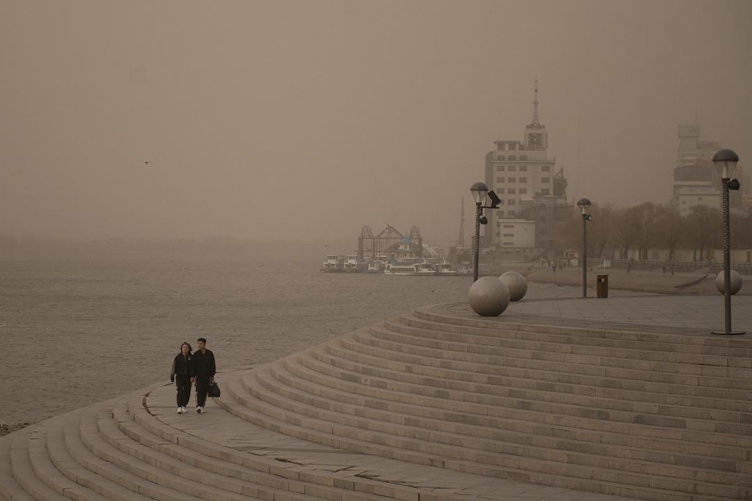 2019年4月16日,中國東北部城市哈爾濱的人們,在沙塵暴中行走。