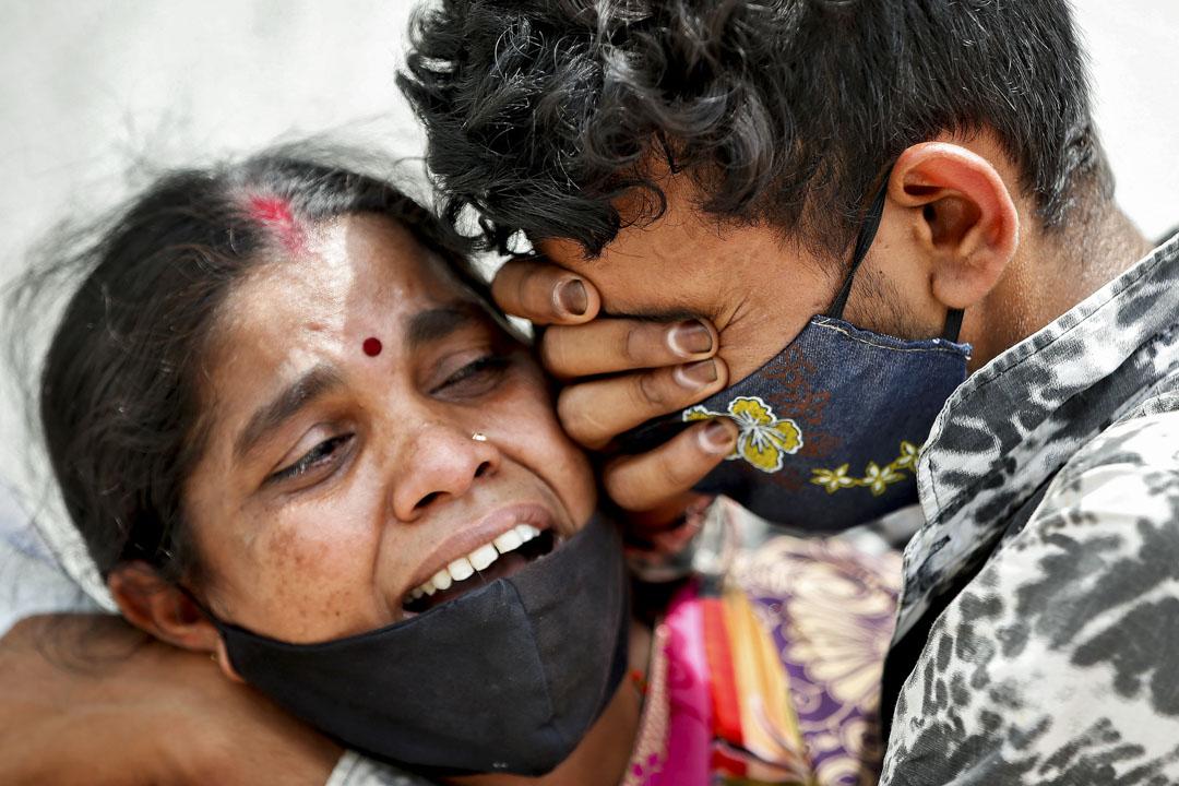 2021年4月20日,印度艾哈邁達巴德一家醫院的停屍房外,一名婦女因丈夫死于新冠病毒而與兒子一同痛哭。