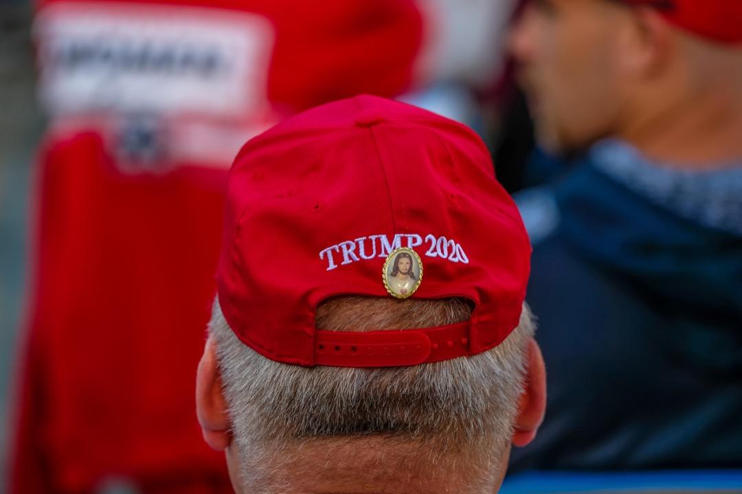 2020年9月18日,美國總統特朗普到賓席法尼亞州進行造勢拉票活動,一名戴上特朗普招牌紅色帽字的支持者在帽子後方扣上耶穌襟章。