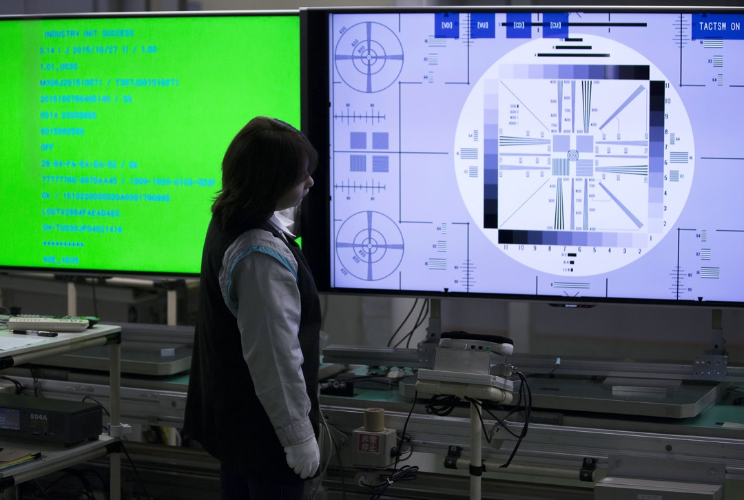 日本栃木縣一家電視工廠,一位工人為液晶顯示屏進行品質檢查。