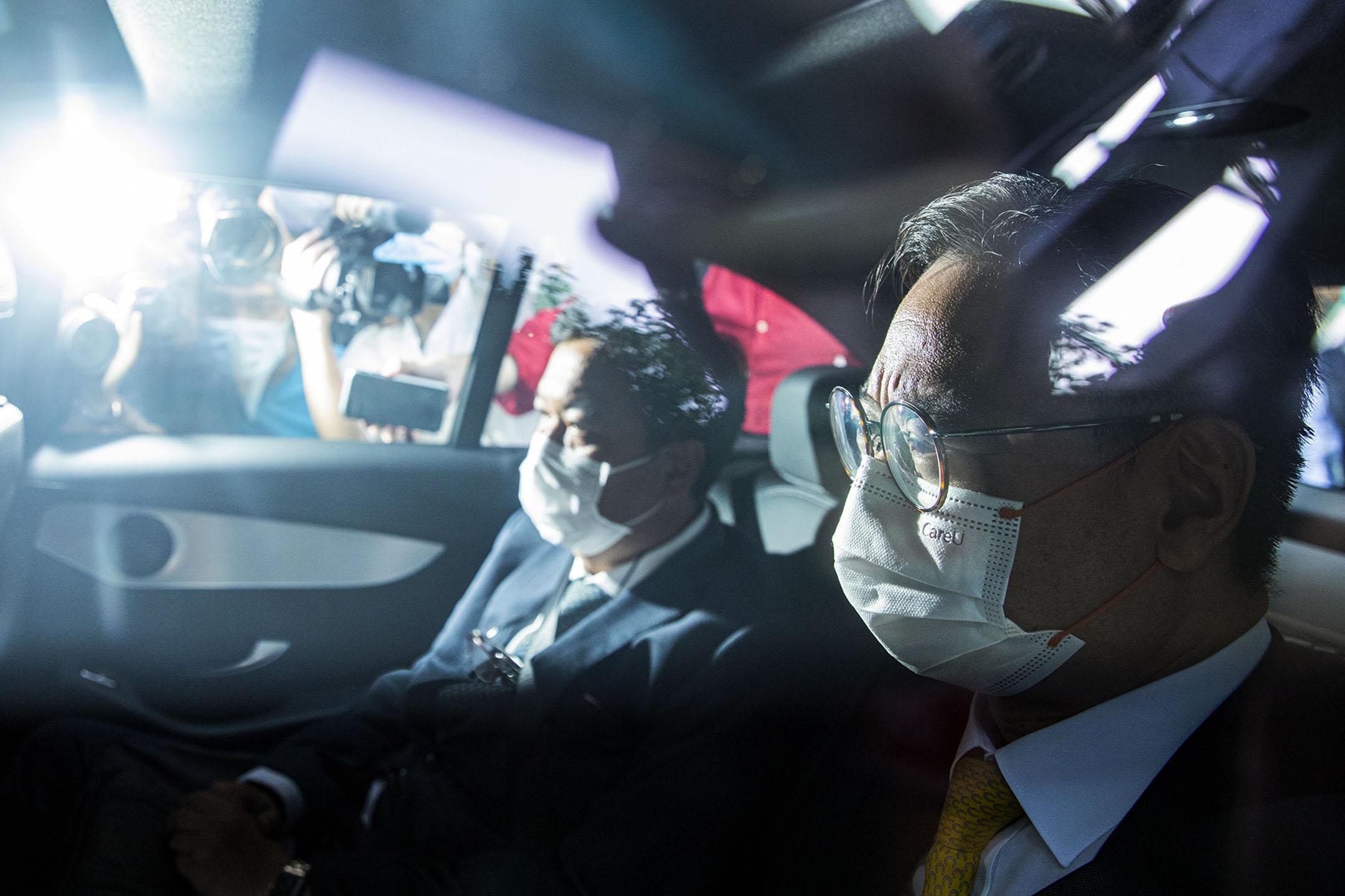 2021年4月7日西九龍裁判法院,李宇軒的代表律師羅達雄(左)、事務律師陳天立(右)乘車離開法院。 攝:陳焯煇/端傳媒
