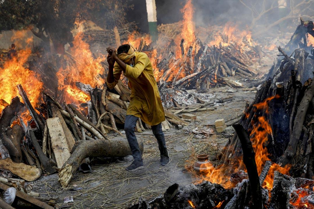 2021年4月26日,印度新德里的一個火葬場,一名男子穿過燃燒中的火堆。