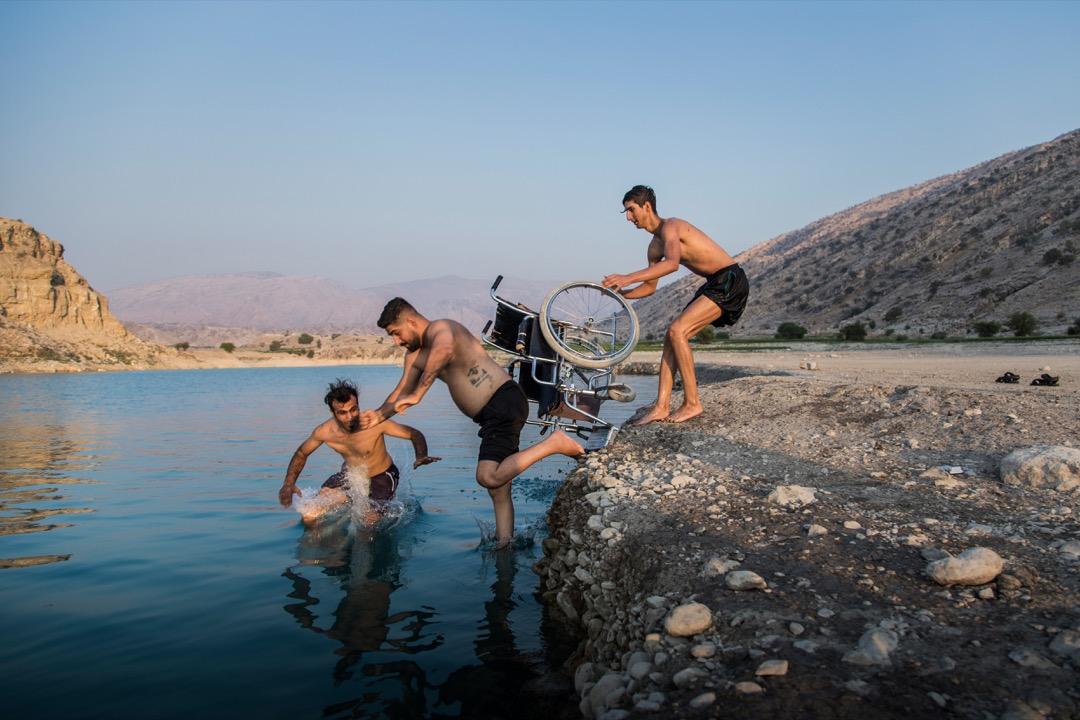 2020年9月9日,伊朗市鎮 Gachsaran,Saeed(中)的兄弟把他從輪椅中推到水塘裏,讓他能一嘗跳水的感覺。