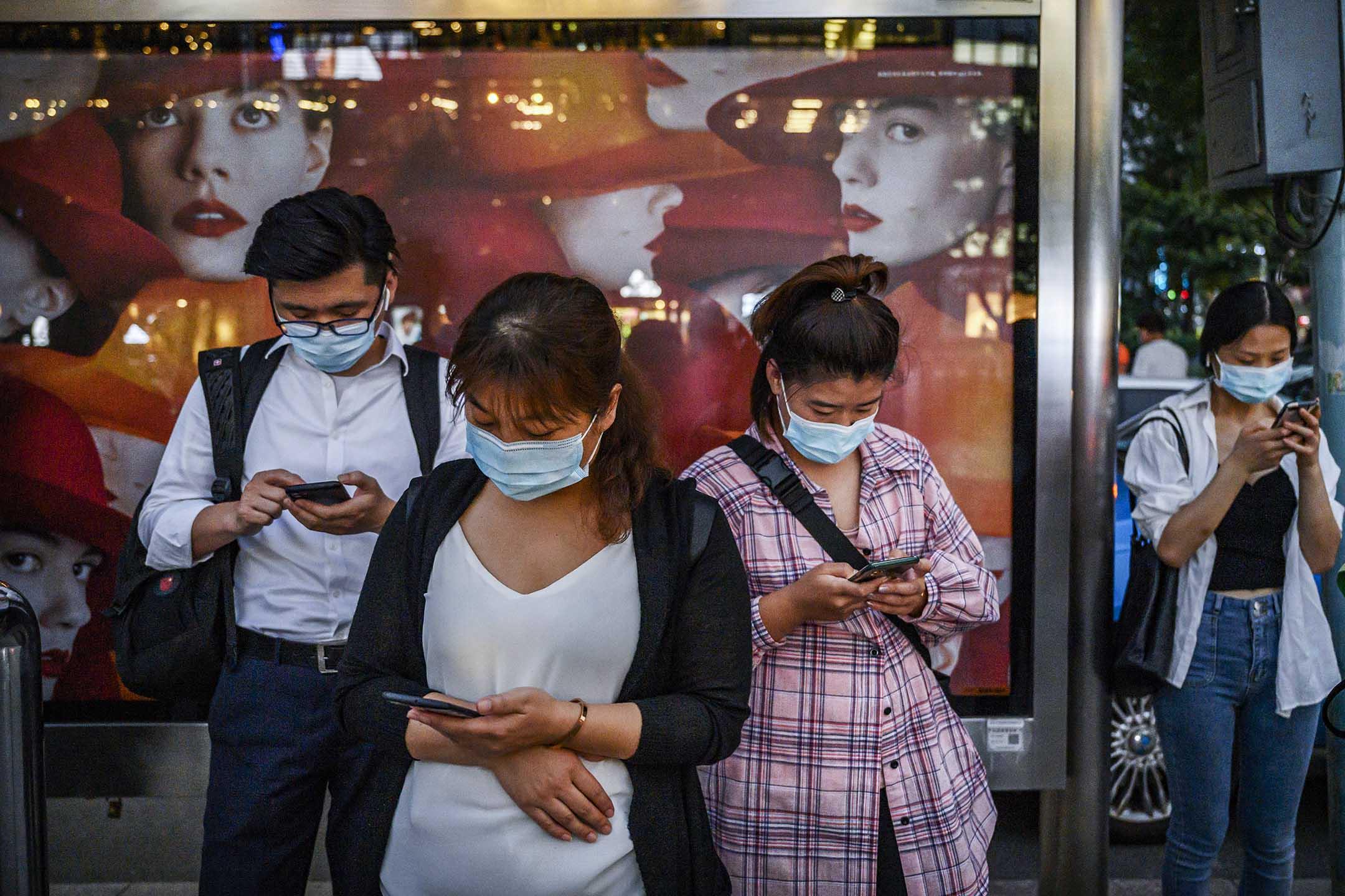 2020年9月21日北京,市民在一個公共汽車站等待時玩手機。 攝:Kevin Frayer/Getty Images