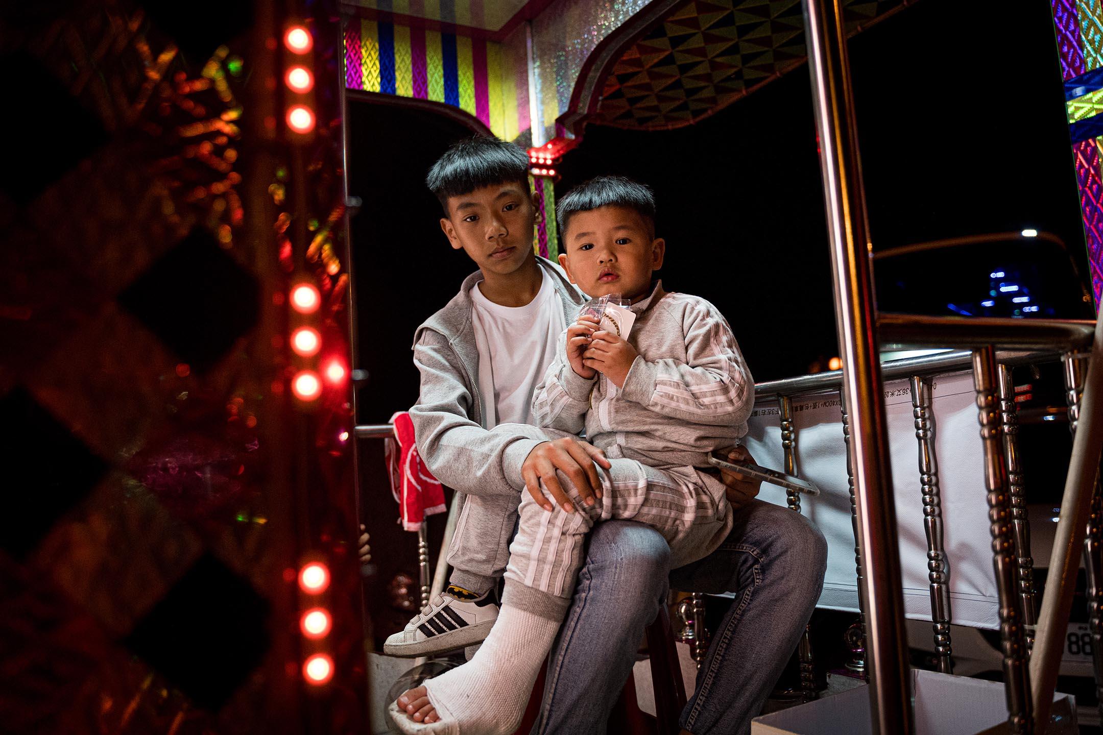 媽祖進香途中,各周邊交好廟宇宮壇會出「陣頭」或邀請傳統戲團共襄盛舉。圖為一對兄弟坐在表演花車上。