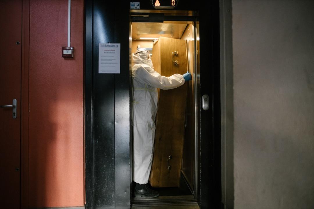 2020年4月23日,法國首都巴黎市郊小鎮龐坦,一名殮房員工在搬運一套棺材。