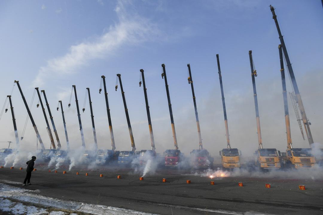 2021年2月19日,遼寧省瀋陽市,正值春節,工人在弔臂車前放炮仗,祝願來年生意興隆。