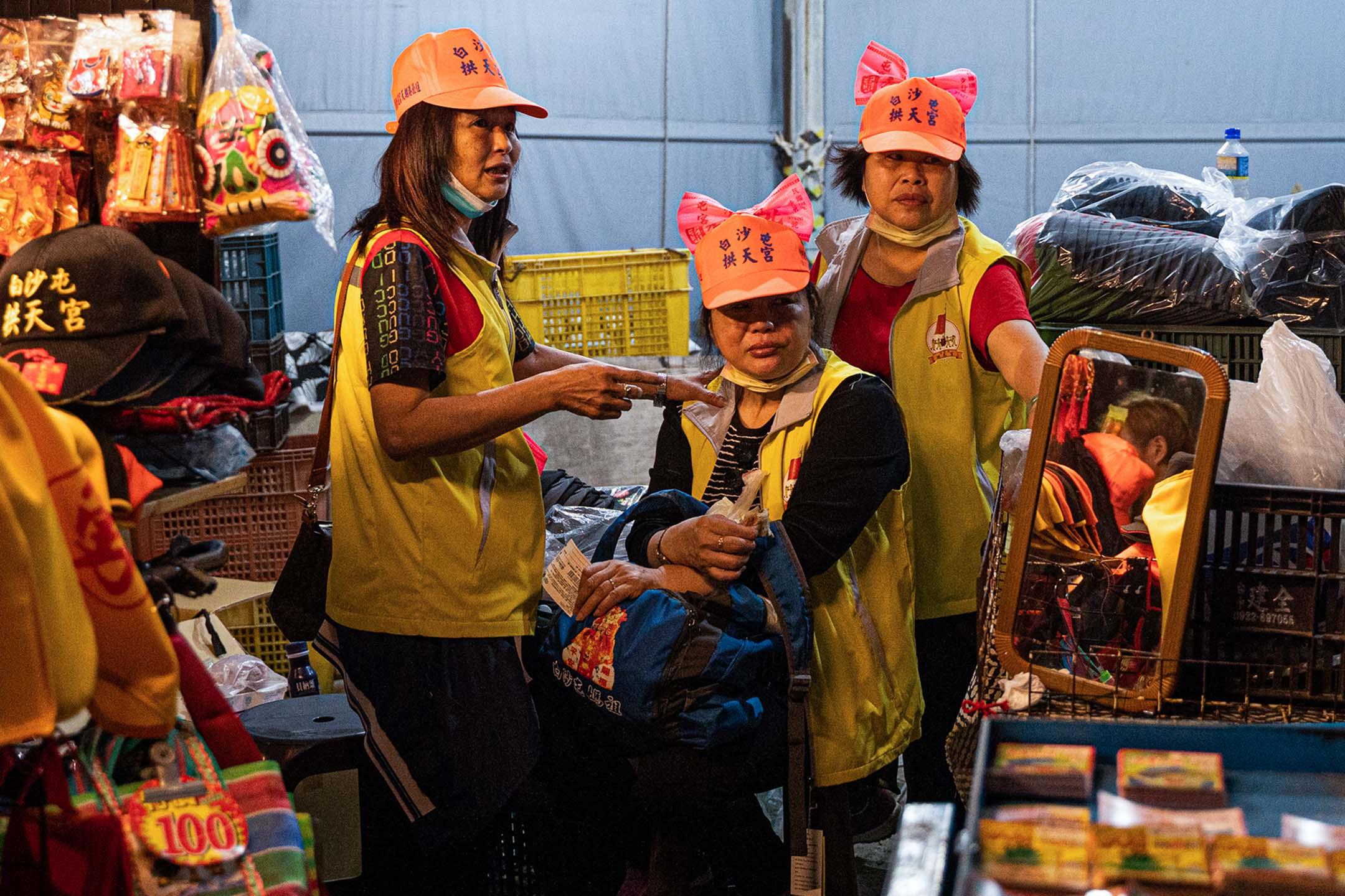 信眾將本次媽祖進香的粉紅臂章折成蝴蝶形狀,掛在帽子上。