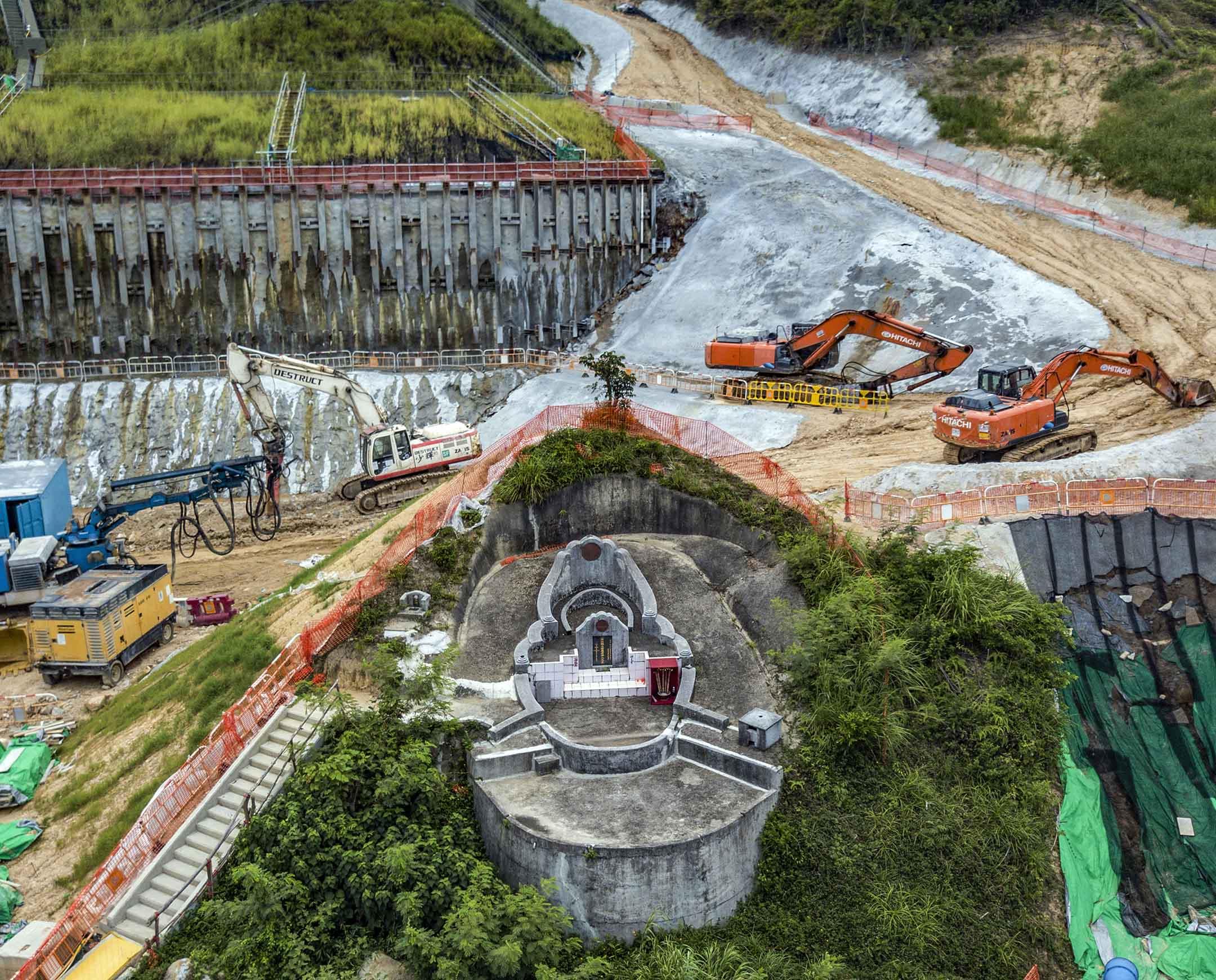 2020年8月9日香港馬鞍山,一個山墳被建築地盤包圍。