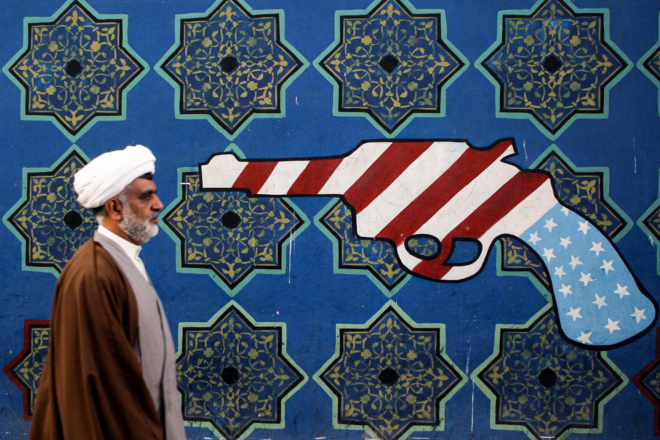 2007年2月22日伊朗德黑蘭,伊朗文職人員走過前美國大使館牆上的壁畫。