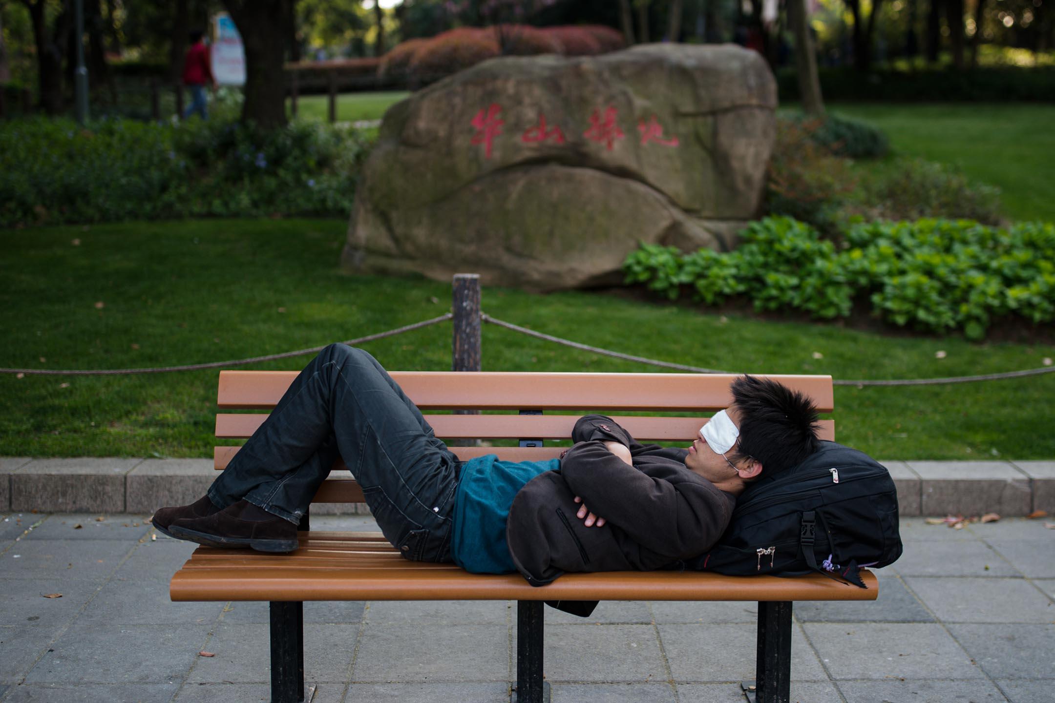 2020年4月08日上海,市民戴著眼罩睡在邊路。 攝:Yves Dean/Getty Images