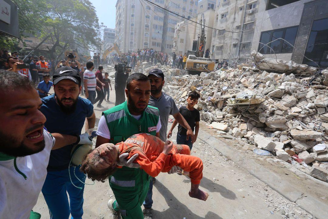 2021年5月16日,以色列空襲後,加沙地帶一名男子抱着一個孩子的屍體。 攝:Ashraf Amra/Getty Images
