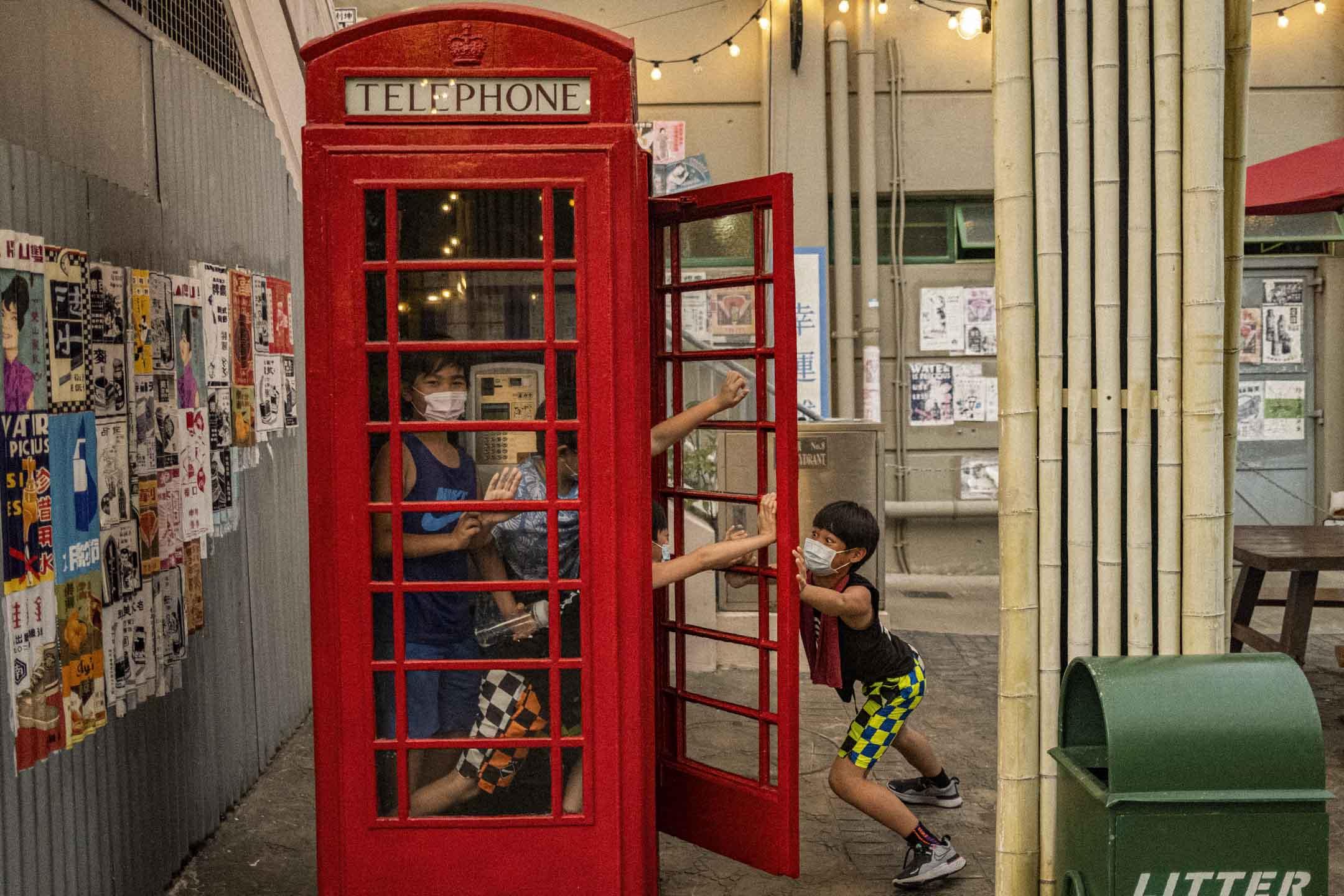 2021年4月1日,孩童在香港老大街的電話亭内玩耍。