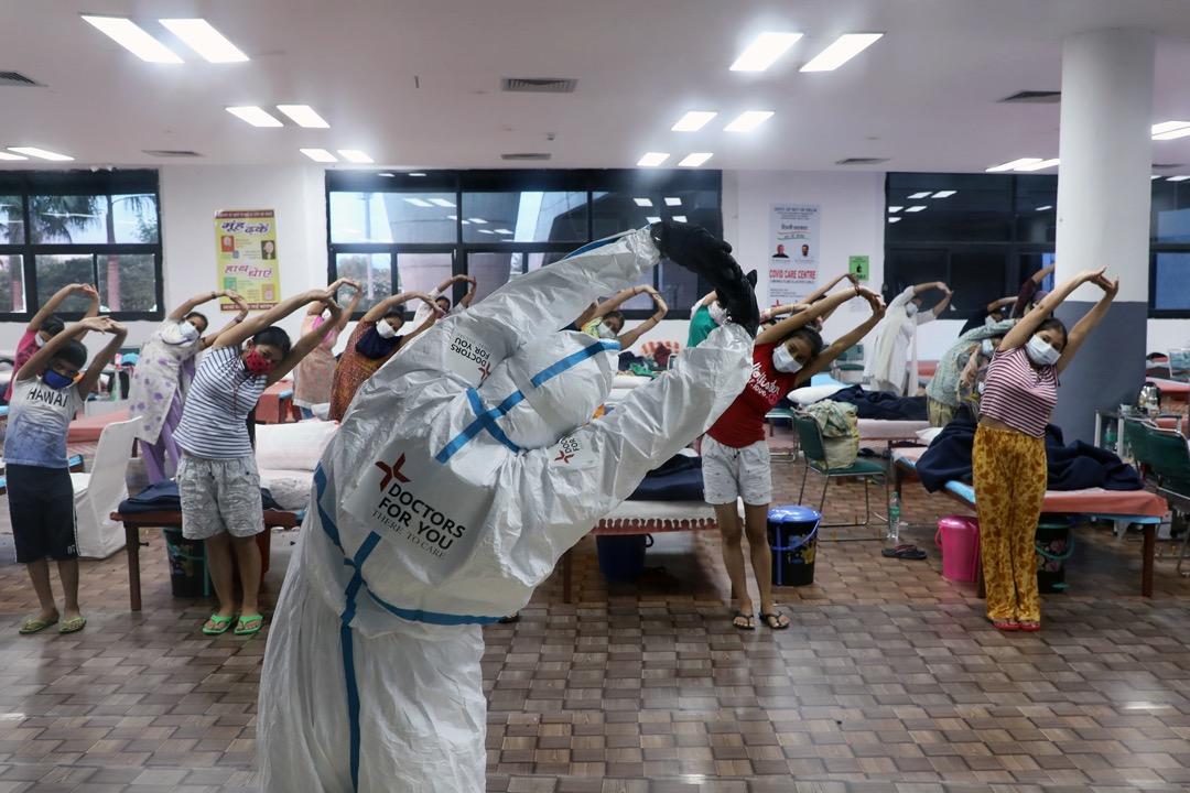 2020年7月30日,印度首都新德里市郊的村落,一名醫護人員為女性病房內的新冠病毒輕症患者帶領伸展訓練。