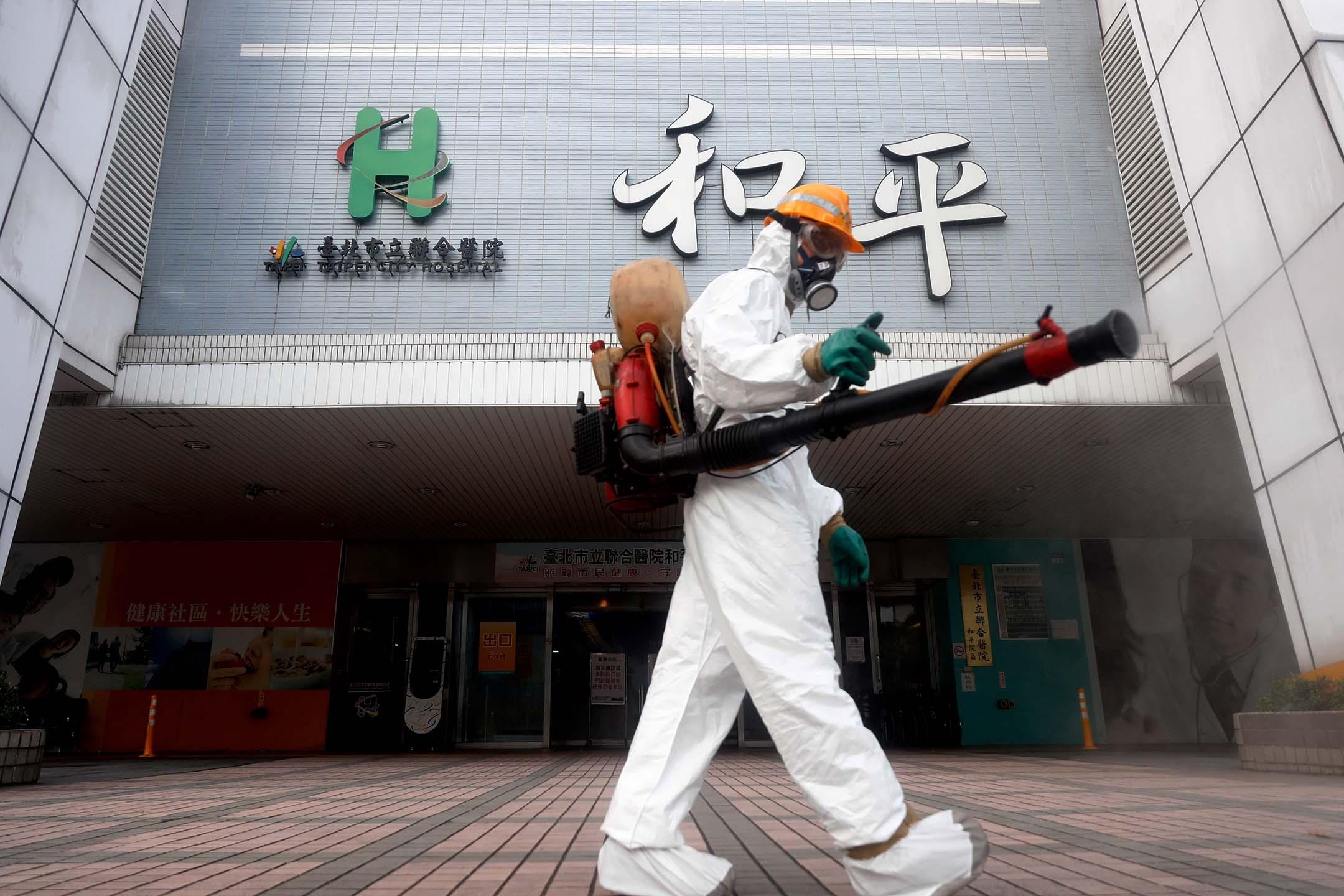 2021年5月15日,一名穿著防護裝備的工作人員為台北的和平家醫院外消毒。