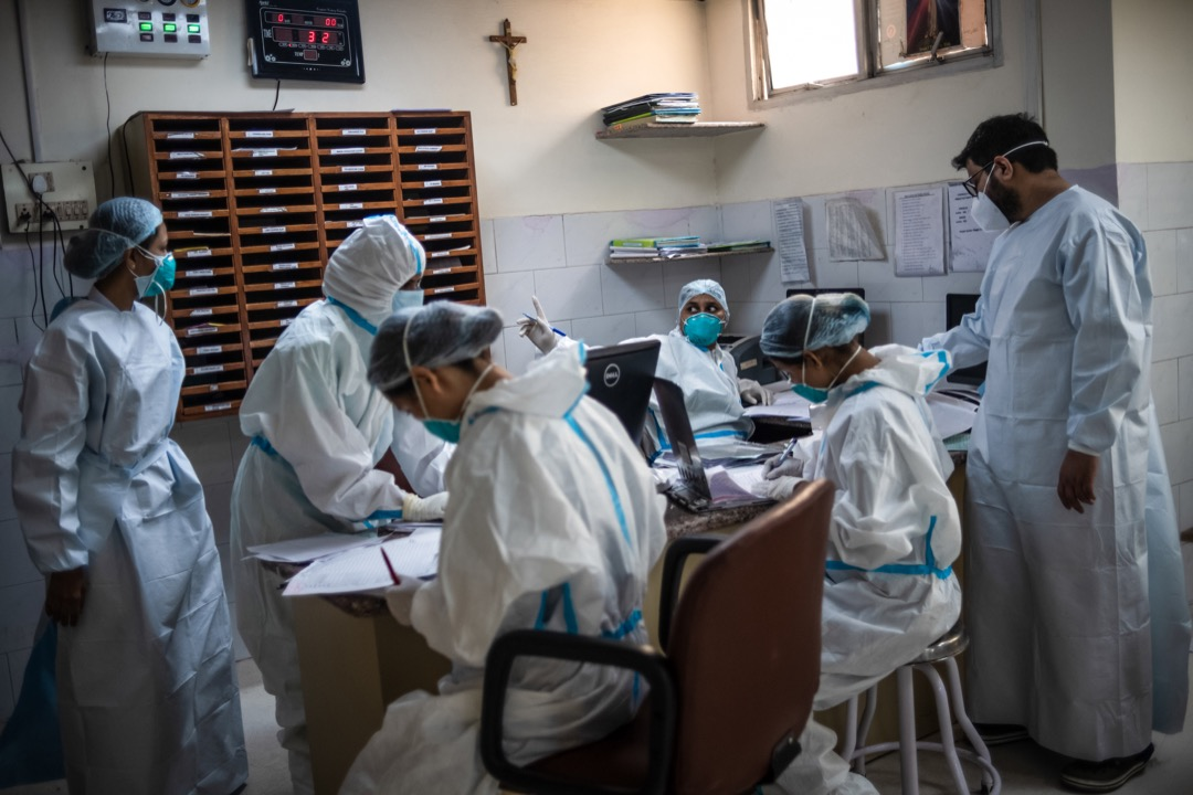 2021年5月6日,印度首都新德里的一家醫院內,醫護人員在辦公室內忙於梳理病人資料。