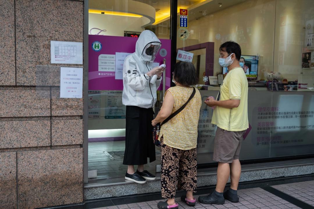 2021年5月27日,台北街頭,一名店員為顧客量度體溫。