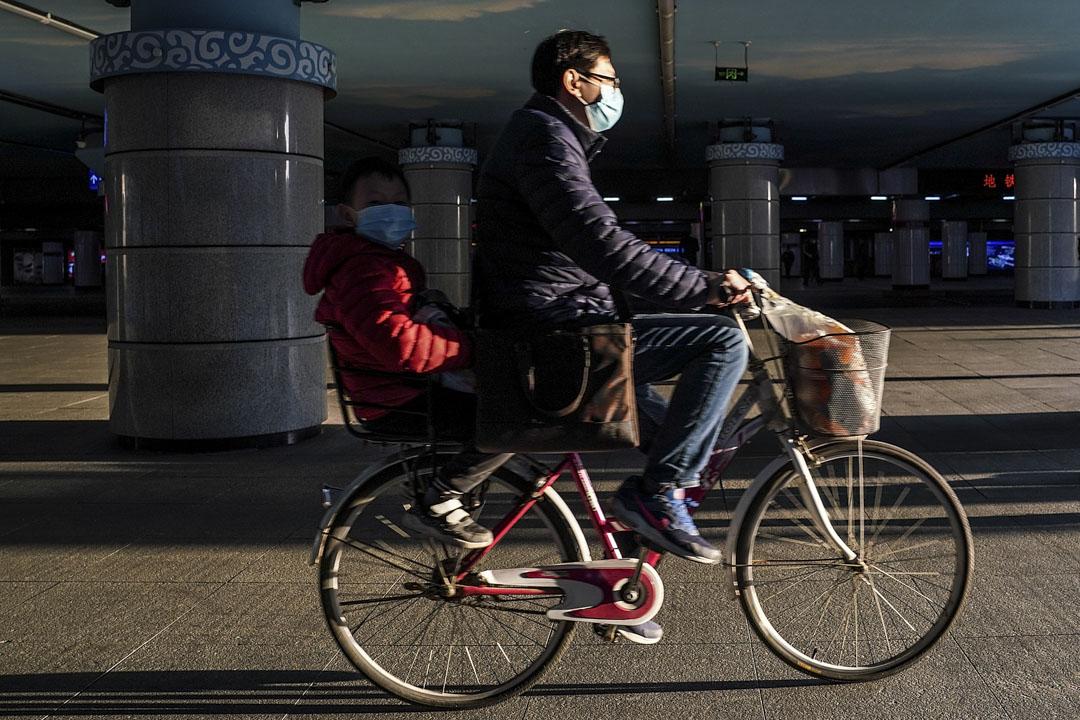 2020年3月27日,一個男子與孩子在街上騎著自行車。