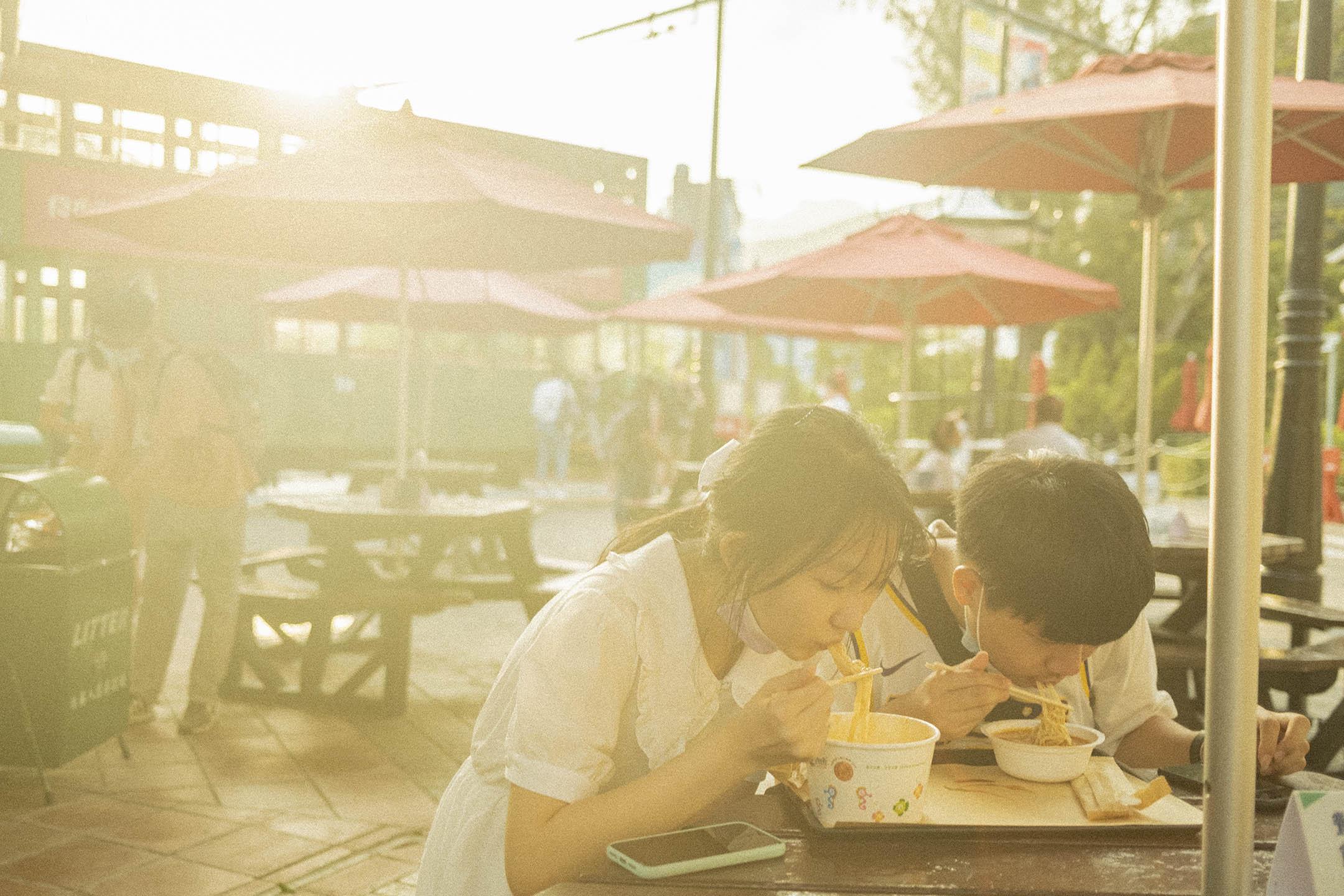 2021年4月25日,一對年輕人黃昏時在香港老大街吃東西。